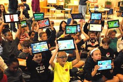 students holding up tablets