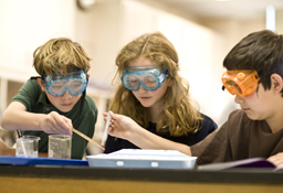 three students with safety goggles on